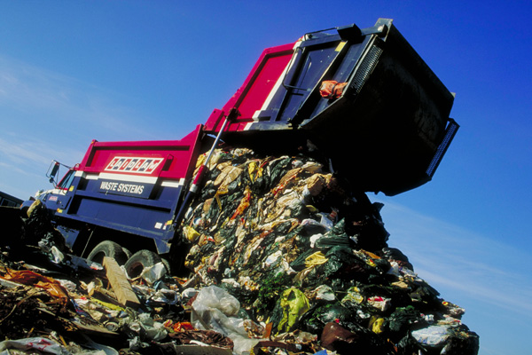 Image of a garbage truck unloading trash at a landfill