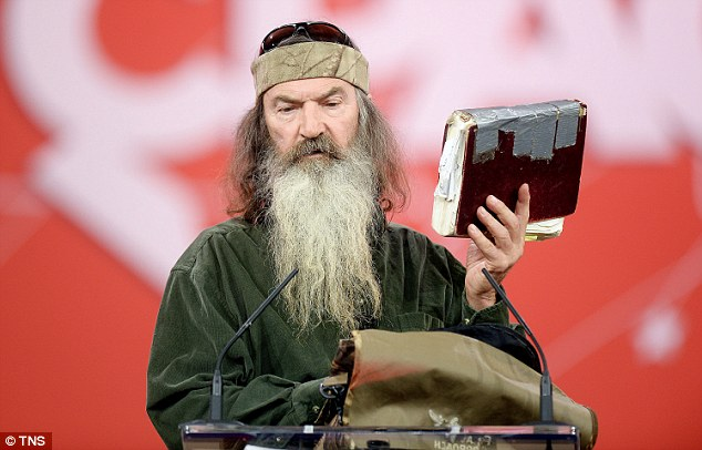 Phil Robertson from Duck Dynasty speaks at a public event holding a well-worn bible held together with Duct Tape.